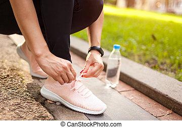 Junge Frau, die ihre Schuhe anschnallt, im Sommerpark bei Sonnenuntergang. Läufer ruht sich aus. Sportkonzept.