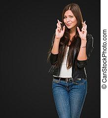 Junge Frau mit gekreuzten Fingern