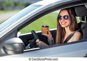 Junge Frau trinkt Kaffee, während sie ihr Auto fährt.