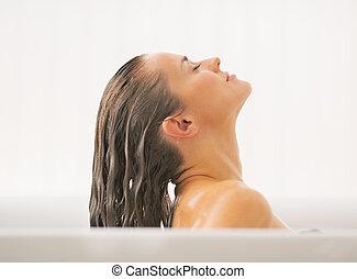 Junge Frau wäscht Haare in der Badewanne.