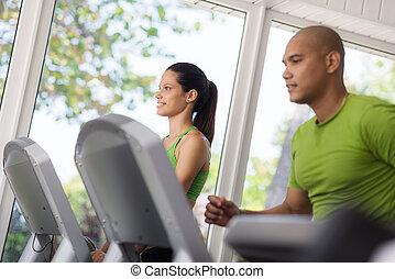 Junge Leute trainieren und laufen im Fitnessstudio