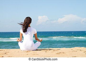 Junge, wunderschöne Frau meditiert