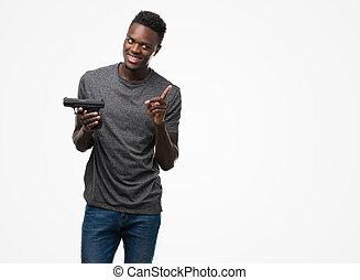 Junger afroamerikanischer Mann mit einer Waffe sehr glücklich mit Hand und Finger auf die Seite.