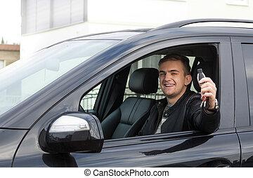 Junger Erwachsener mit Autoschlüsseln.