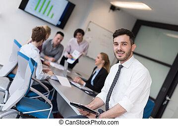 Junger Geschäftsmann mit Tafel im Büro-Meetingraum