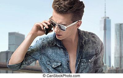 Junger, gutaussehender Mann mit stilvoller Sonnenbrille.