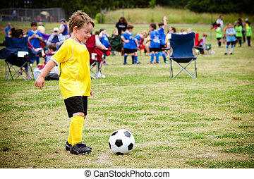 Junger Junge, der Fußball spielt während des Spiels.