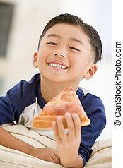 Junger Junge isst Pizzascheibe im Wohnzimmer und lächelt