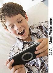 Junger Junge mit handfestem Spiel drinnen