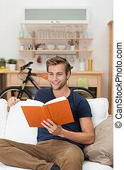 Junger Mann entspannt sich, ein Buch zu lesen