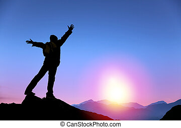Junger Mann steht auf dem Gipfel des Berges und beobachtet den Sonnenaufgang.