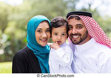 Junges arabisches Familienporträt draußen.