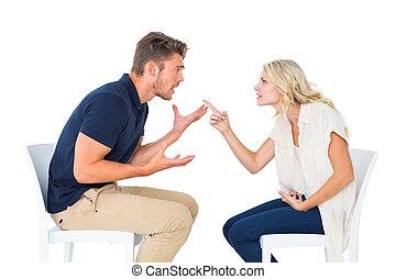 Junges Paar, das in Stühlen sitzt.