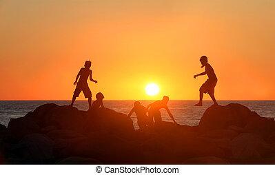 Jungs spielen am Strand.