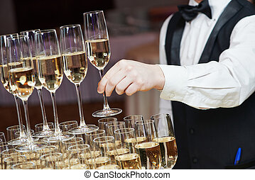 Kellner mit Glas Champagner.