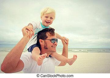 Kind und Vater sind glücklich am Strand