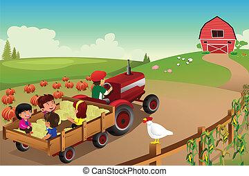 Kinder auf einer Heufahrt in einer Farm während der Herbstsaison.