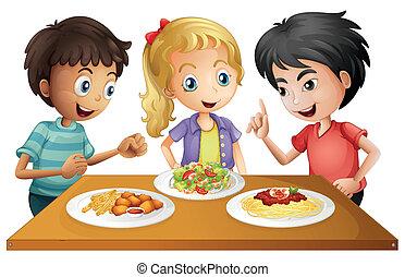 Kinder, die den Tisch mit Essen beobachten.