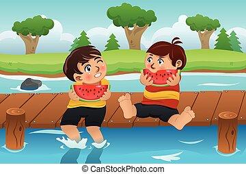 Kinder essen Wassermelone.