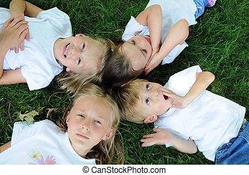 Kinder spielen auf dem Rasen