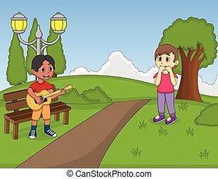 Kinder spielen Gitarre im Park.