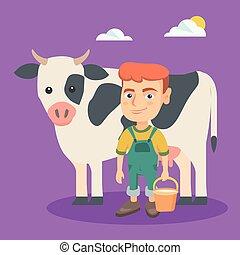 Kleiner weißer Farmerjunge, der eine Kuh melkt.