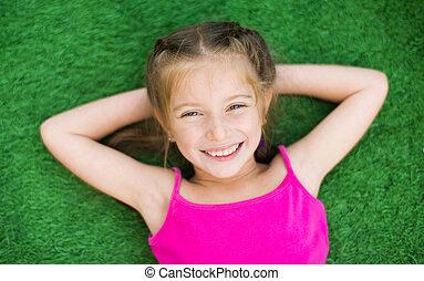 Kleines Mädchen auf grünem Gras.