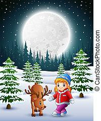 Kleines Mädchen, das nachts mit einem Hirsch im Schneegarten spielt.