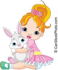 Kleines Mädchen umarmt Spielzeughäschen