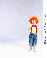 Komisches Bild von dem kleinen Clown, der große Seifenblasen macht.