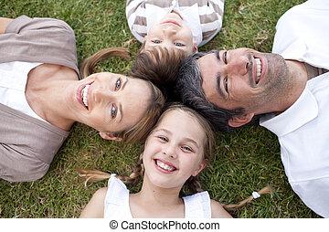 Lächelnde Familie liegt draußen