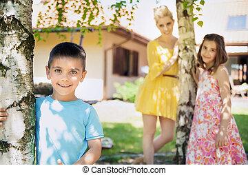 Lächelnde Familie spielt im Garten