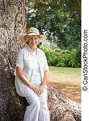Lächelnde Rentnerin, die auf dem Baumstamm sitzt