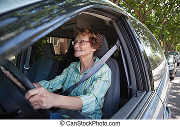 Lächelnde Seniorenfrau im Auto