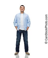 Lächelnder Mann mit Händen in Taschen.