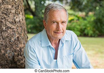 Lächelnder Rentner, der auf dem Baumstamm sitzt
