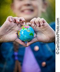 Lächelndes Mädchen, das Globus in Händen hält, gefaltet in Herzform.