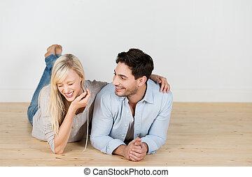 Lachendes junges Paar liegt auf dem Boden