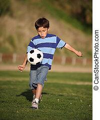 Latino-Junge spielt mit Fußball