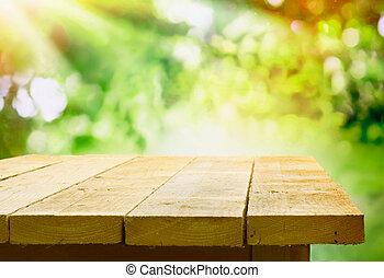 Leerer Holztisch mit Gartenbokeh