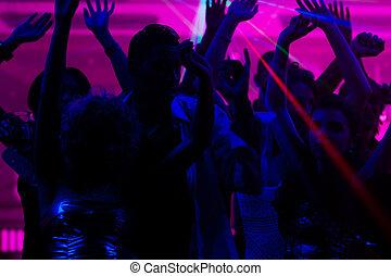 Leute, die im Club mit Laser tanzen