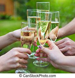 Leute mit Champagnergläsern machen einen Toast draußen