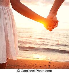 Liebe - romantisches Paar mit Händen, Sonnenuntergang am Strand