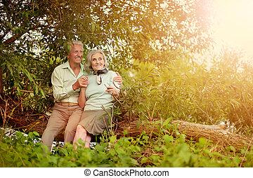 Liebes erwachsenes Paar, das auf einem Baumstamm sitzt.
