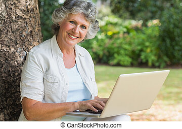 Lustige reife Frau, die einen Laptop benutzt, der auf einem Baumstamm sitzt.