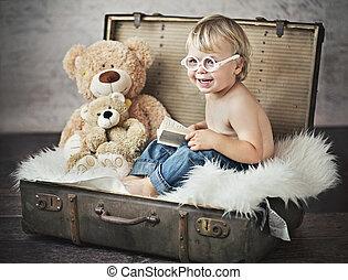 Lustiges Foto von dem kleinen Jungen im Koffer