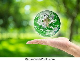 Männliche Hand halten Planeten auf verschwommenem, grünen bokeh Hintergrund der Baum Natur : Weltumwelt-Tag Konzept: Elemente dieses Bildes von der NASA eingerichtet.