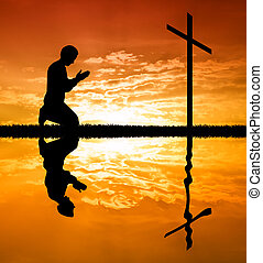 Mann betet unter dem Kreuz.