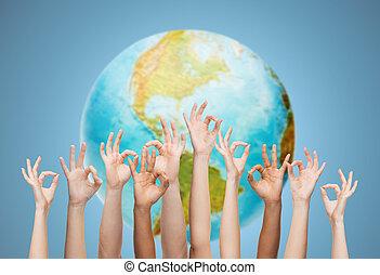 Menschliche Hände zeigen ok Zeichen über Erdkugel.