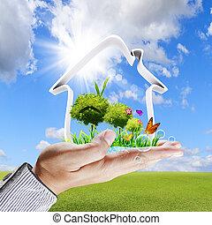 Menschliche Hand zeigt ein grünes Hauskonzept